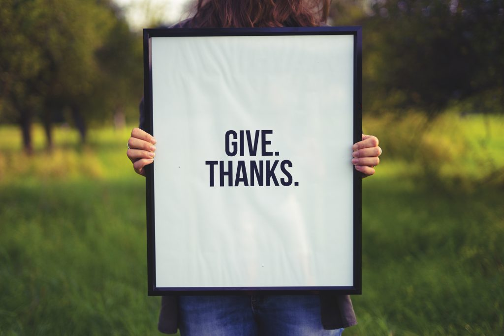 """a girl holding a sign that says """"give thanks"""""""